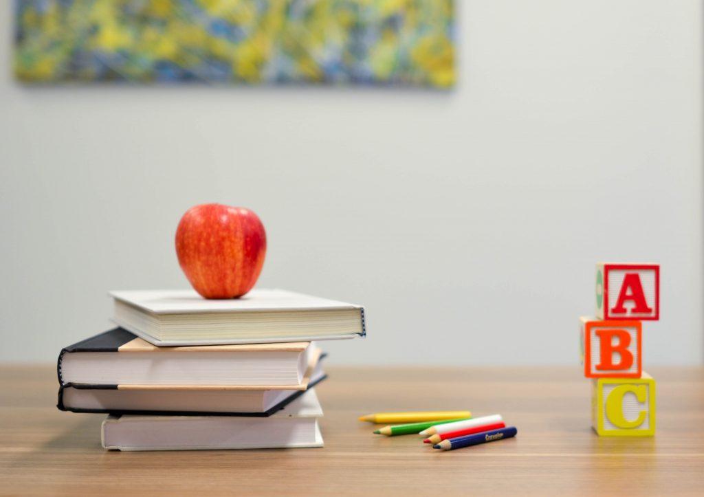 buecher-mit-apfel-auf-lehrertisch